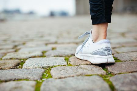 female jogger: Pierna de corredora caminar sobre el pavimento. Enfoque de zapatos. Pies de la mujer en la acera. Foto de archivo