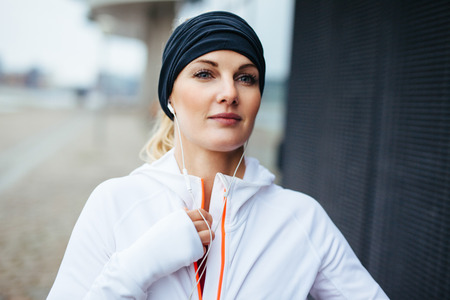 sports wear: Woman preparing herself for a run. Focused young fitness model in sports wear.