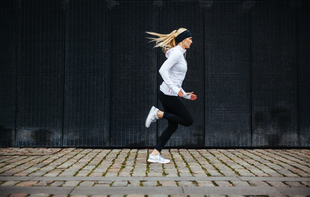 jogging: Side view of sporty young woman running on sidewalk in morning. Health conscious concept with copy space.