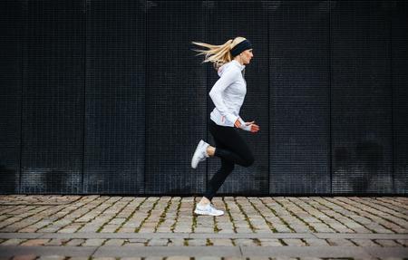 hacer footing: Vista lateral de la mujer joven deportiva corriendo en la acera en la ma�ana. Concepto consciente de la salud, con copia espacio.