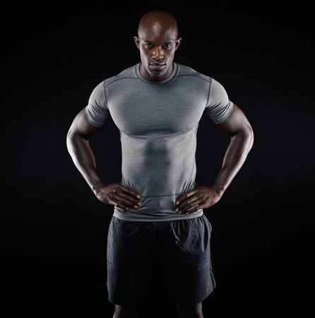 Portrait of muscular young man in sportswear standing with his hands on hips against black background. Strong african athlete.