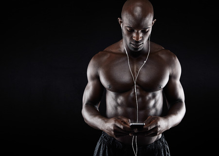 only men: Studio shot of muscular young man listening music on mobile phone against black background. African bodybuilder listening music on earphones.