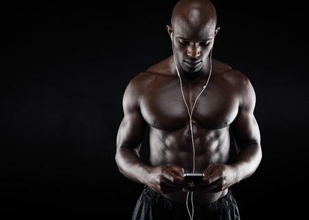 fitness men: Tiro del estudio de la m�sica joven muscular hombre escucha en el tel�fono m�vil contra el fondo negro. Culturista africana escuchar m�sica con aud�fonos. Foto de archivo