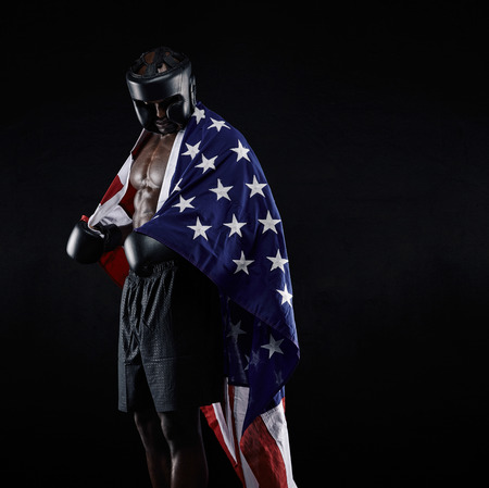 draped: Portrait of african american Boxer with the American flag draped around his body against black background