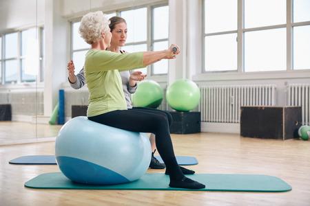 Vrouwelijke trainer assisteren senior vrouw tillen gewichten in de sportschool. Senior vrouw zittend op pilates bal doet het gewicht oefening wordt bijgestaan door persoonlijke trainer bij healthclub.