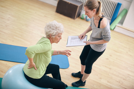 back exercise: Senior woman sitting on a fitness ball with her female instructor explaining exercise plan at gym. Physical therapist with old woman at rehab.
