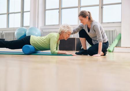 tercera edad: Mujer mayor que ejercita con un rodillo de espuma siendo asistido por el instructor personal en el gimnasio. Terapeuta f�sico ayuda a la mujer de edad avanzada en su entrenamiento en el club de salud.