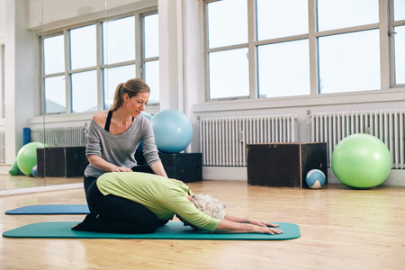 Female trainer helping senior woman doing yoga. Elder woman bending over a exercise mat with personal instructor helping at gym.
