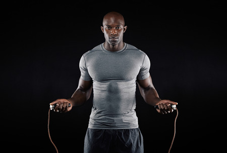 Masculine man skipping rope in dark. Portrait of muscular young man exercising with jumping rope on black background