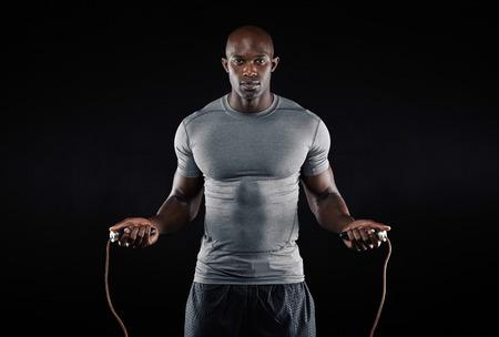 Hombre masculino saltar la cuerda en la oscuridad. Retrato de hombre joven y musculoso ejercicio con saltar la cuerda en el fondo negro