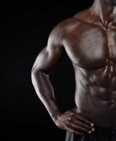 sin camisa: Close-up foto de joven africano hombre musculoso cuerpo contra el fondo negro. Modelo masculino descamisado con estructura muscular.