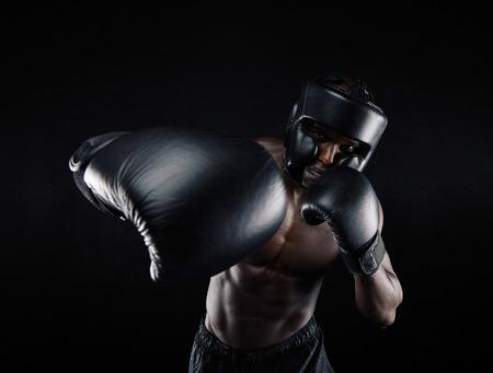 boxeador: Retrato del varón africano practicando boxeo contra el fondo negro. Boxeador de sexo masculino lanzando un puñetazo en la frente. Joven boxeo entrenamiento deportista.
