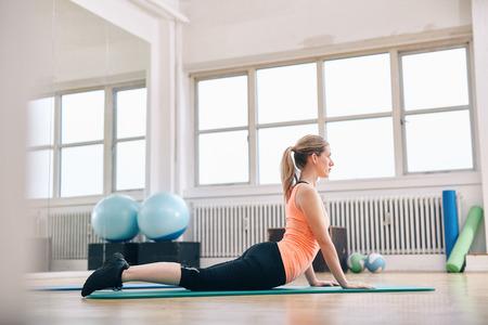 Vrouw doet kern stretch op fitness mat. Aantrekkelijke jonge vrouw doet yoga op gymnasium.