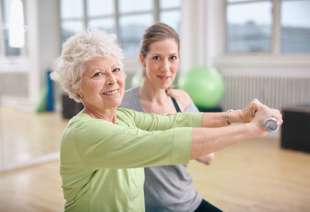 physical: Senior woman exercising with fitness trainer at gym. Active senior woman lifting dumbbells with help from personal trainer.