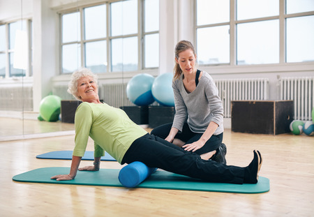 trainer: Senior woman doing pilates on the floor with foam roller. Elder woman exercising being assisted by personal trainer at gym.