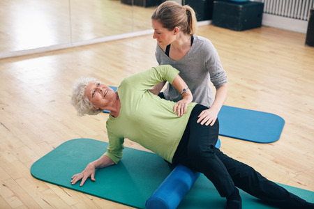 Physical therapists assisting senior woman to perform myofascial release technique with a foam roller to inhibit overactive muscles at gym. Stock Photo