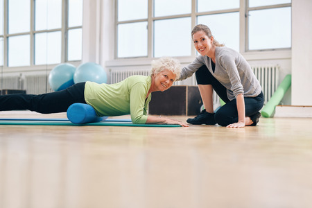 Senior woman exercising on a foam roller with a personal trainer at gym.  Gym coach helping elderly woman in her workout at health club. Stock Photo
