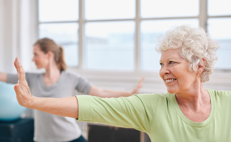 active: Portrait of happy senior woman practicing yoga at gym class. Elderly woman stretching her arms . Stock Photo