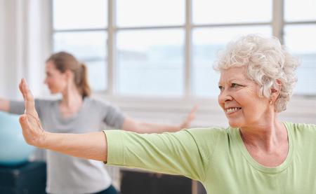 Portret van gelukkig senior vrouw het beoefenen van yoga op de gymles. Bejaarde vrouw stretching haar armen.