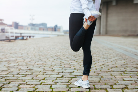 stretches: Low section view of fit young woman stretching her leg before a run in city streets. Preparation for running workout. Stock Photo