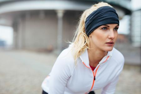 vrouwen: Portret van jonge vrouwelijke atleet leunt over en wegkijken. Gemotiveerd en gefocust sportieve vrouw voor een run.