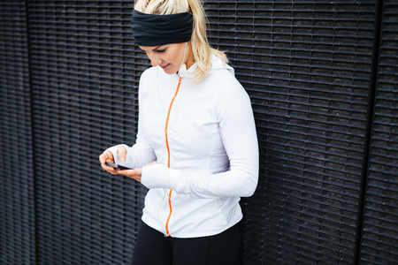 sport training: Image of young woman taking a break form workout using mobile phone outdoors.