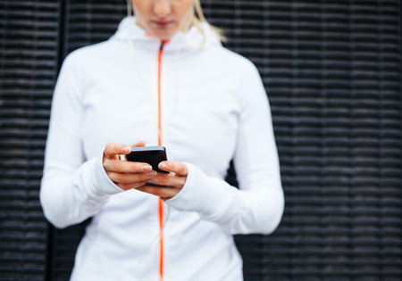 Cropped image of woman in sportswear using mobile phone. Focus on hands and smart phone.