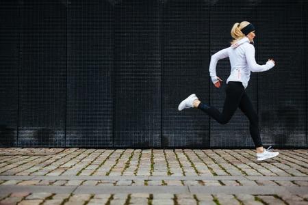 gente corriendo: Vista de la mujer joven que se ejecutan en la acera en la ma�ana. Concepto consciente de la salud, con copia espacio.