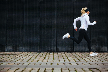 View of young woman running on sidewalk in morning. Health conscious concept with copy space. Banque d'images