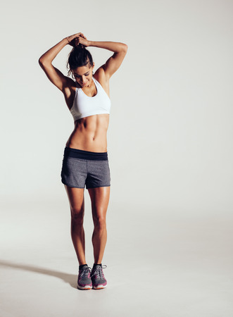 athlete woman: Full length shot of muscular young fitness model in studio. Healthy young woman in sportswear standing on grey background.