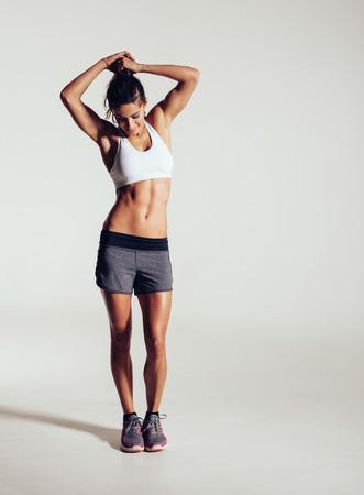 mujer deportista: Tiro integral de modelo de la aptitud joven musculoso en estudio. Mujer joven sana en ropa deportiva de pie sobre fondo gris.