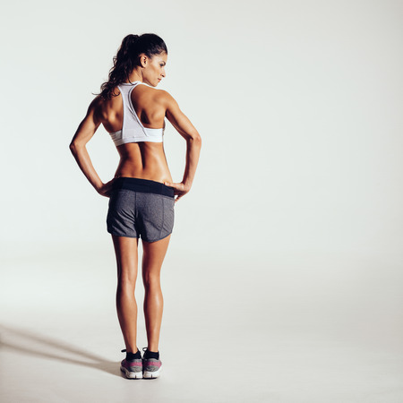hand on hip: Rear view shot of a healthy young woman in sportswear. Full length image of muscular female model standing looking away at copyspace on grey background