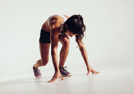 fitnes: Dopasuj kobieta-sportowiec gotowy do uruchomienia na szarym tle. Kobieta fitness model przygotowuje się do sprintu. Zdjęcie Seryjne