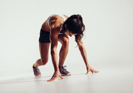 sprint: Fit female athlete ready to run over grey background. Female fitness model preparing for a sprint.