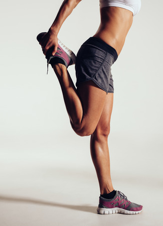 stretches: Cropped image of a fit female runner stretching her legs against grey background. Female athlete doing stretches.
