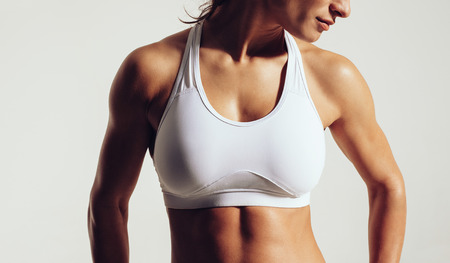 woman bra: Portrait of fit woman in sports bra with muscular body against grey background. Close-up studio shot of female fitness model in sports wear.