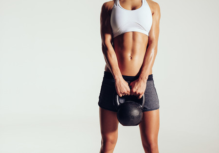 Cropped shot of young woman in sportswear holding a kettle bell. Strong fitness female exercising crossfit with kettlebell in studio. Female model with muscular and slim body on grey background with copyspace. Stock Photo