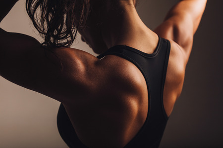 Close-up shot of back of female fitness model. Young woman in sports wear with muscular body. Banque d'images
