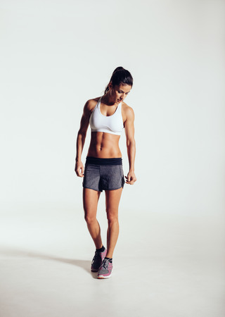 sports wear: Full length portrait of fit young woman in sports wear looking down while standing on grey background. Muscular fitness model.