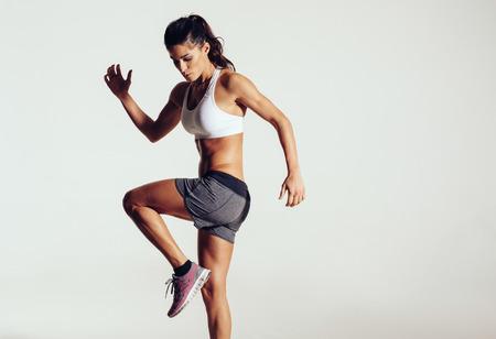 Attraktiv fit kvinna utövar i studio med copyspace. Bild av friska unga kvinnliga idrottare gör fitness träning mot grå bakgrund. Stockfoto
