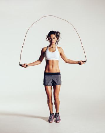 Fit jonge vrouw springtouw. Portret van gespierde jonge vrouw te oefenen met springtouw op het grijze witte achtergrond. Stockfoto