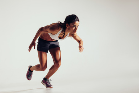 physical: Energetic young woman running over grey background. Focused young female athlete running.