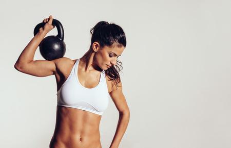 muscular: Atleta joven atractivo, con cuerpo musculoso ejercicio crossfit. Mujer en ropa deportiva haciendo entrenamiento crossfit con campana hervidor de agua sobre fondo gris.