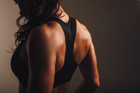fitness model: Rear view of strong young woman wearing sports bra. Muscular back of a woman in sportswear.