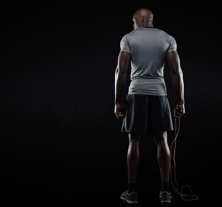 Rear view of muscular man standing with jumping rope on black background. Studio shot of fitness model holding skipping rope looking at copy space. Stock Photo