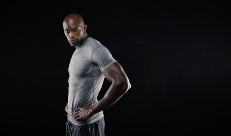 Portrait of handsome young muscular man posing against black background. African male fitness model looking at camera with his hands on hips with copyspace. photo