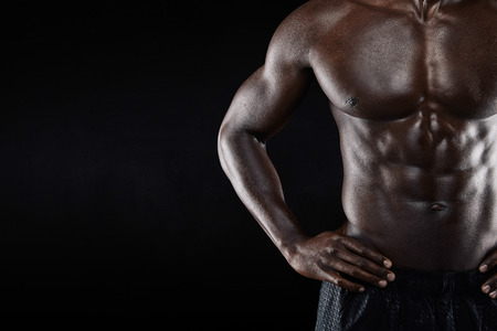 strong arm: Close-up of shirtless african man with hands on hip while standing against black background. Cropped image of torso of a muscular man with copyspace. Stock Photo
