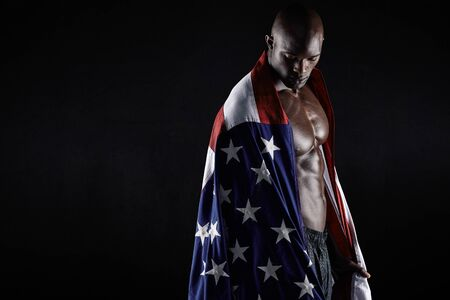 Portrait of muscular man wrapped in the American flag with copy space on black background. African athlete with country flag.