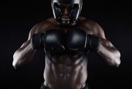 Portrait of young african male boxer preparing for competition against black background. Muscular male model wearing boxing gear practicing. photo