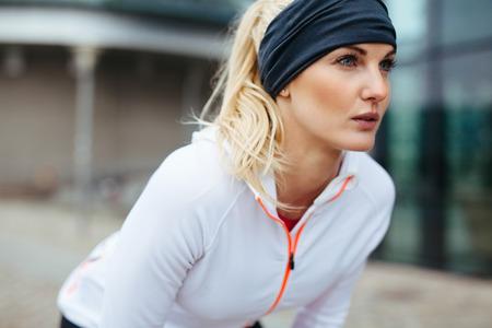 若い女性はスポーツ用品の上に傾いた。楽しみにして実行するための断固としたスポーツ女性。
